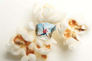 Художник, вдохновлённый кинокартинами, фигачит рисунки прямо на попкорне.